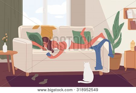 Apathetic Young Woman Lying On Sofa In Messy Room Or Apartment And Surfing Internet On Smartphone. L