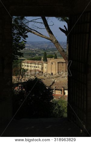 ancient Tuscan walled city houses with towers and stone walls and paved cobbled streets in Italy poster