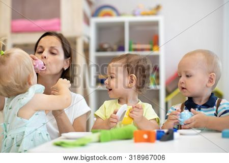 Nursery Children Playing With Teacher In The Classroom Or Creche