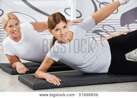 Two smiling women doing fitness training together in gym