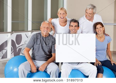 Happy senior people on gym balls holding empty poster in fitness center