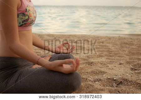 Lotus Yoga Pose. Close Up. Focus On One Hand. Yoga At The Beach. Young Woman Sitting On Sand, Medita