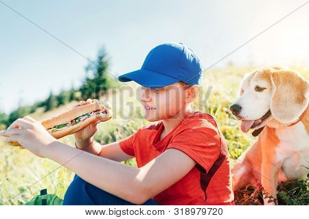 Little Smiling Boy Weared Baseball Cap With A Huge Baguette Sandwich With His Beagle Dog Friend Duri