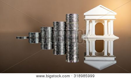 Banking Concept. Bank Account Interest Rate Growth. Bank Model Woth Coins Stacked On Glossy Table.