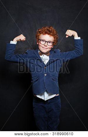 Strong Little Child Boy On Blackboard Background