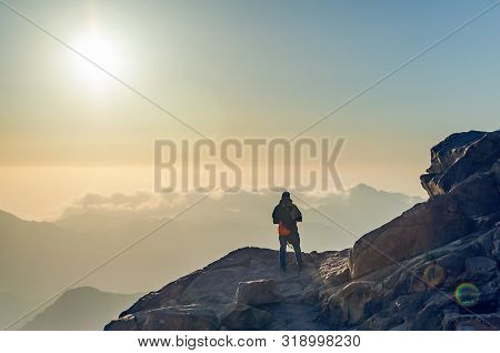 A man stands on the edge of a cliff on Mount Moses and looks at the sunrise in the mountains of Egypt. poster