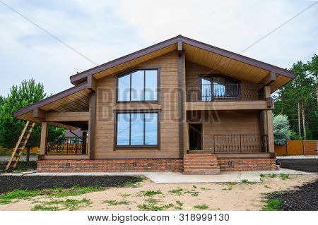 Facade Of New House Under Construction, Unfinished Wooden Home Painted With Brown Natural Color.