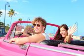 Couple happy in vintage retro convertible car. Friends driving on summer road trip in pink car. Beautiful young Caucasian man and Asian woman smiling joyful on sunny summer day traveling. poster