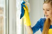 Young woman in yellow gloves cleaning window with blue rag and spray detergent. Spring cleanup, housework concept poster