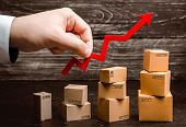 Businessman holds a red arrow up above cardboard boxes folded incrementally. Increase sales and production rate of goods and products. Profit growth, business development. Increase in export volumes. poster