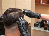 Hairstylist working with scissors and comb, close up view. Stylists hands in black rubber gloves. Interior of hairdressing saloon. Stylist and client. Selective soft focus. Blurred background poster