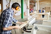 Back view portrait of mature carpenter cutting wood in joinery workshop, copy space poster