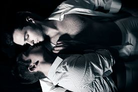 Gay Male Lovers Lying In Bed Holding And About To Kiss