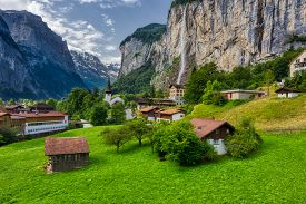 View Of Lauterbrunnen Town In Swiss Alps Valley With Gorgeous Staubbach Waterfalls In The Background