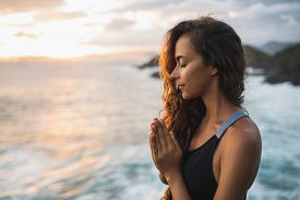 Young Woman Praying And Meditating Alone At Sunset With Beautiful Ocean And Mountain View. Self-anal