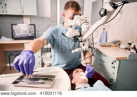 Close Up Of Male Dentist Hand In Sterile Glove Holding Metal Dental Explorer While Checking Female P