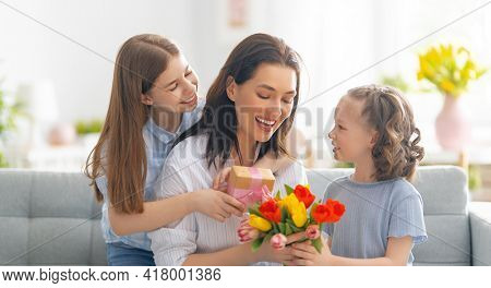 Happy mother's day! Children daughters are congratulating mom and giving her flowers. Mum and girls smiling and hugging. Family holiday and togetherness.