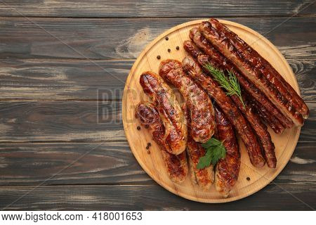Grilled Sausages On Wooden Board On Brown Background. Top View