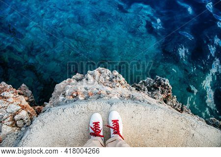 Above Shot Of White Shoes Standing Of The Rock With Beautiful Azure Waters In The Spanish Island Of