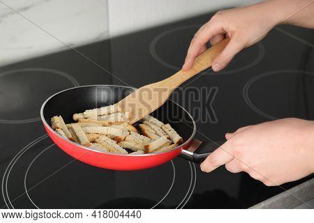 Woman Cooking Hard Chucks On Cooktop, Closeup
