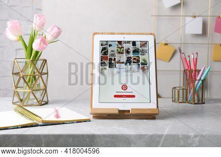 Mykolaiv, Ukraine - April 12, 2021: Ipad With Pinterest App On Grey Marble Table In Office