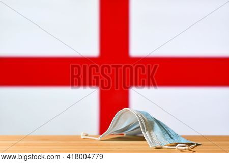 A Medical Mask Lies On The Table Against The Background Of The Flag Of England. The Concept Of A Man