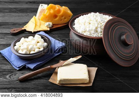 Clay Dishware With Fresh Dairy Products On Black Wooden Table