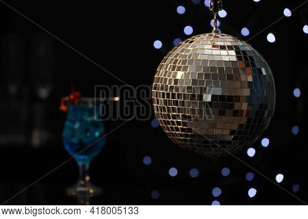 Shiny Disco Ball Hanging Over Bar Counter With Cocktail In Nightclub, Space For Text