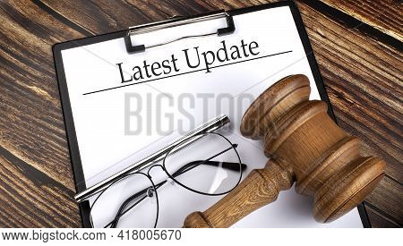 Paper With Latest Update With Gavel, Pen And Glasses On The Wooden Background