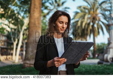 Successful Young Business Woman Useing  Digital Tablet While Walking In Summer Park Barcelona,  Hips