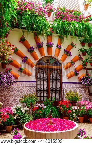 The Courtyard Of The House, With Flowers In Pots On The Floor And On The Walls With A Fountain. Cord