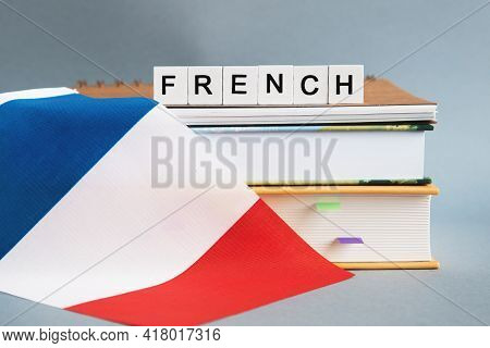 The Inscription French On A Stack Of Textbooks, Books, Exercise Books And National Flag Of France, T