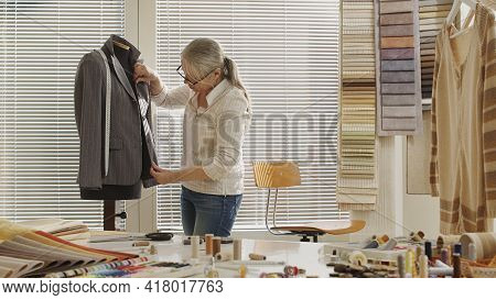 Woman Dressmaker Working With Measure Tape And Tailoring Mannequin, Adjusting The Jacket. Her Studio