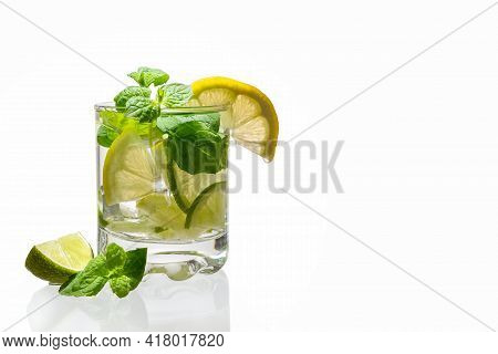 Citrus Lemonade With Ice In A Glass Decorated With Lemon, Lime And Mint Slices And On A White Backgr