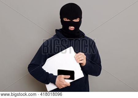 Satisfied Man Robber Steals Laptop Beech And Phone, Being Dressed In Robber Mask And Black Turtlenec