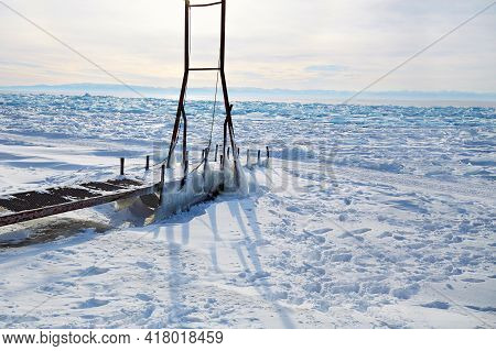 Icy Pier, A Device For Launching A Boat Into The Lake. Frozen Lake Baikal, Hummocks.