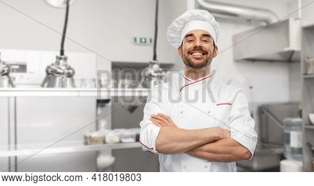 cooking, culinary and people concept - happy smiling male chef in toque and jacket over restaurant kitchen background
