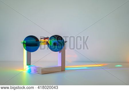 Blue Reflective Sunglasses On Wooden Stand In Front Of A White Background With Rainbow Reflections O