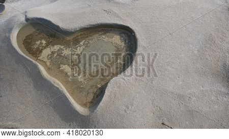 Deepening Relief In The Form Of Craters On Limestone And Rock Near The Sea. In The Form Of A Heart.