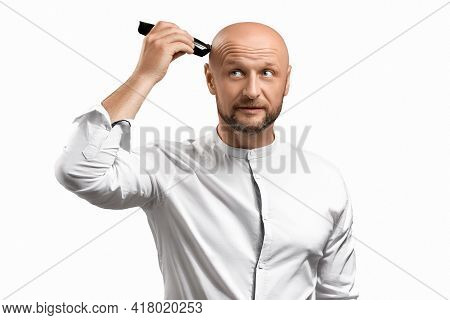 The Concept Of Baldness And Alopecia.a Bearded Man Holds A Hair Clipper And Shaves Off The Hair On T