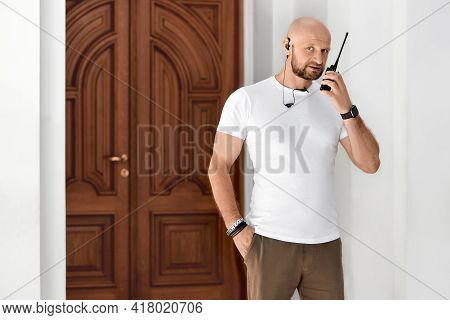 A Security Guard With A Walkie-talkie, A 40-year-old Bald Man, Talks On A Walkie-talkie In The Lobby