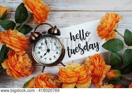 Hello Tuesday Card And Alarm Clock With Orange Flower Decoration On Wooden Background