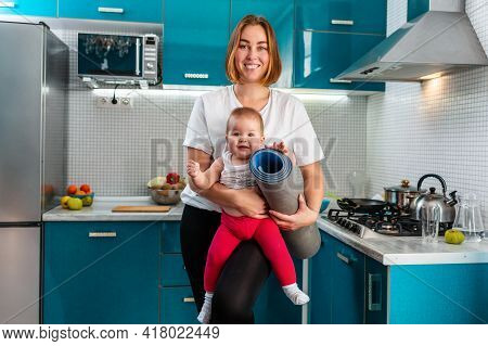 Portrait Of A Young Happy Mother Holds Her Baby In Her Arms, And A Sports Mat Rolled Up. In The Back