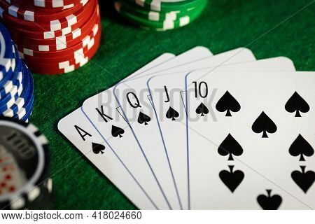 Royal Flush In Poker Game. Cards With Casino Chips On Green Cloth