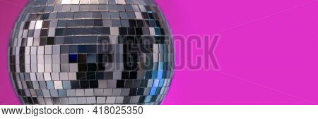 Shining Disco Ball party music event equipment on pink wall background