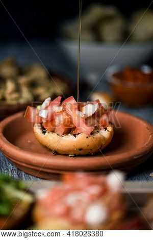 a spurt of olive oil falls on an appetizer, made with bread topped with raw chopped tomato and onion, on a gray rustic wooden table next to some dishes with different vegan appetizers and side dishes