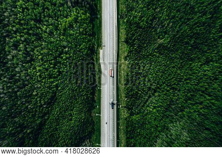 Aerial View Of Toll Road Highway With Cars And Trucks Through Green Summer Forest