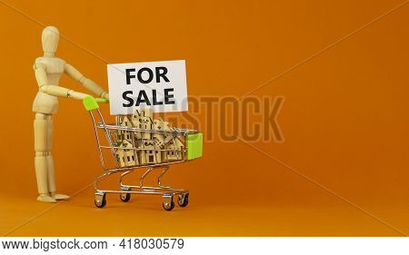 House For Sale Symbol. Miniature Shopping Cart With Wooden Houses, Words For Sale. Wooden Model Of H