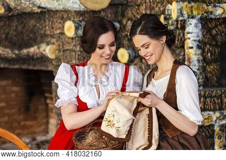 Two Lovely Smiling Caucasian Ladies Working With Spinning Wheel And Fancywork Hoop In Rural Environm