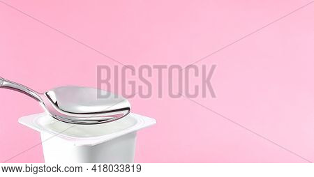 Yogurt Cup And Silver Spoon On Pink Background, White Plastic Container With Yoghurt Cream, Fresh Da
